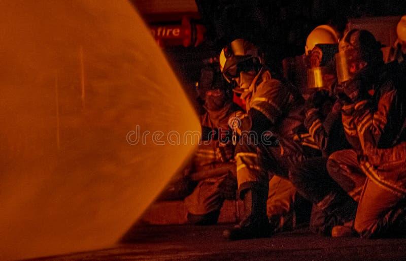 Pompieri che attaccano un fuoco immagine stock