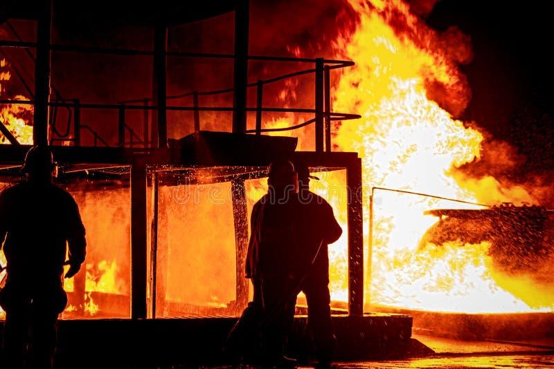 Pompieri che lavorano ad un fuoco immagini stock libere da diritti