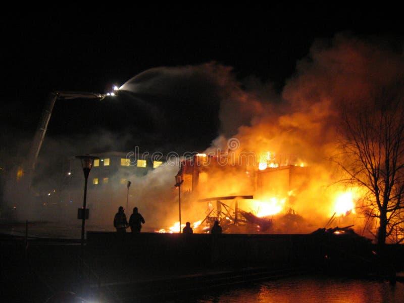 Pompieri che mettono casa fuori bruciante. fotografia stock