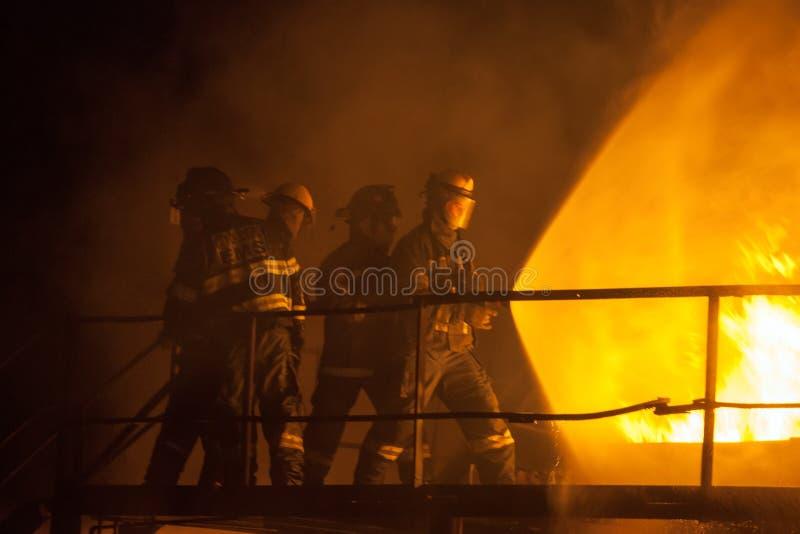 Pompieri che usando spruzzo pieno per mettere fuori un fuoco durante l'esercizio antincendio fotografie stock