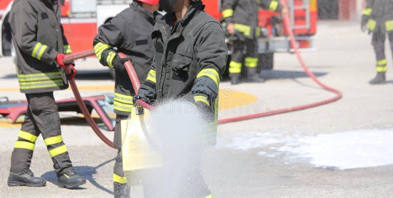 Pompieri con l'estintore durante il sessio di pratica fotografie stock libere da diritti