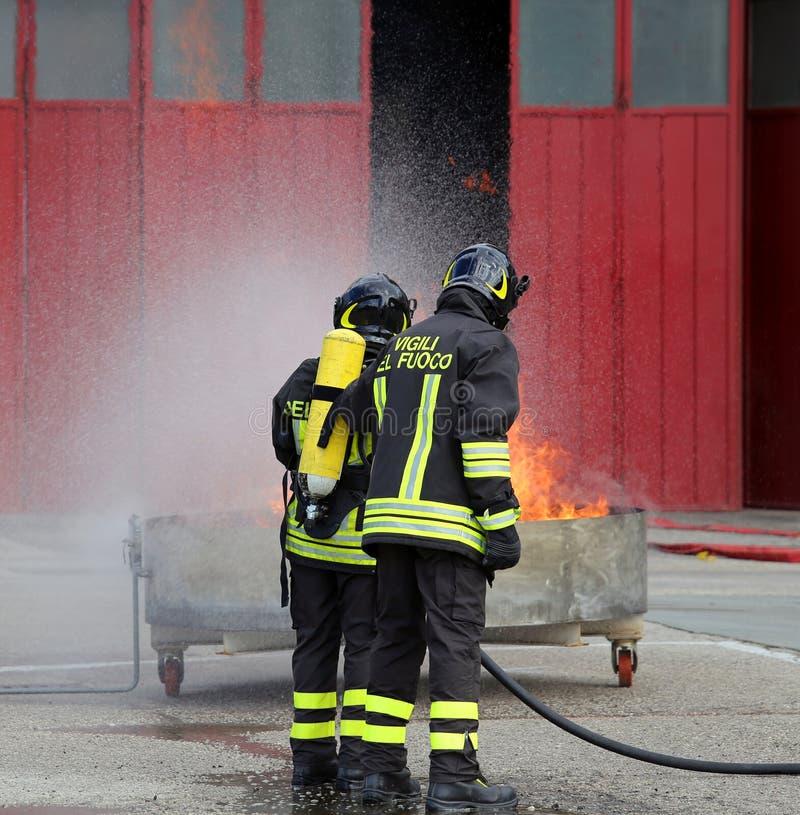 Pompieri con le bombole d'ossigeno fuori dal fuoco durante l'addestramento immagine stock libera da diritti