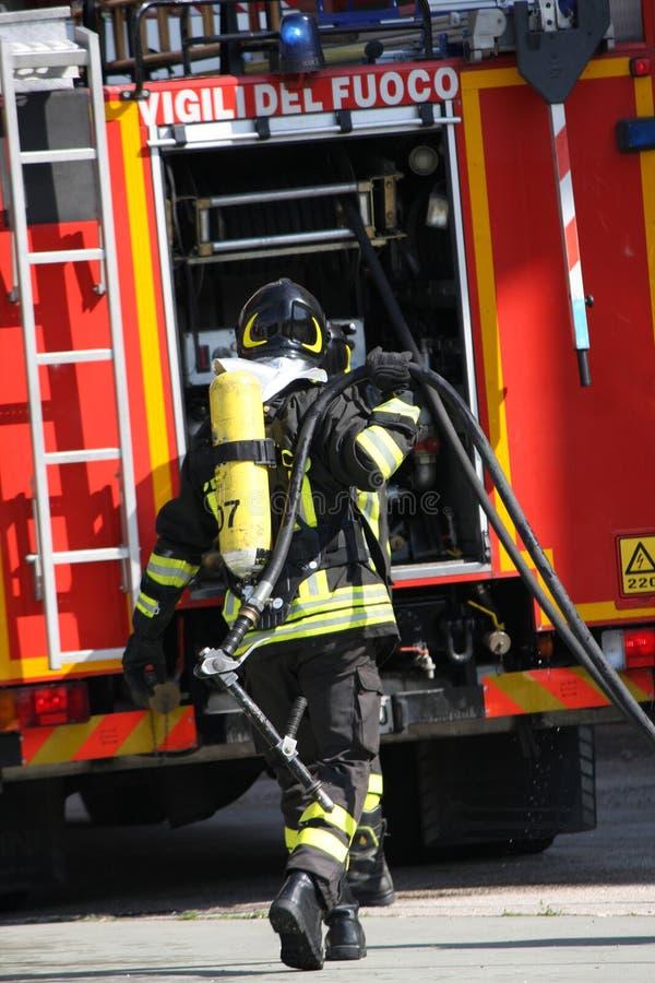 Pompieri coraggiosi con il fuoco del carro armato di ossigeno durante l'esercizio tenuto immagine stock libera da diritti
