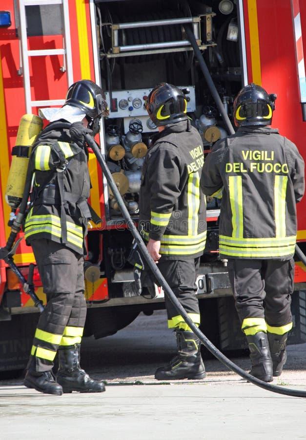 Pompieri coraggiosi con il fuoco del carro armato di ossigeno durante l'esercizio tenuto fotografie stock libere da diritti