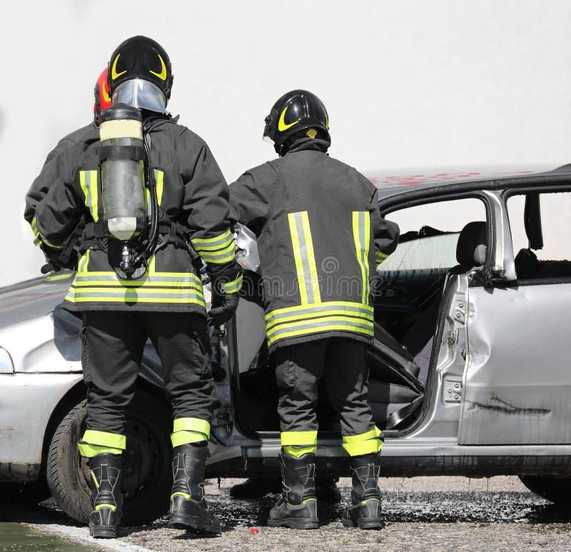 Pompieri durante l'operazione con i cilindri dopo il ro fotografia stock libera da diritti