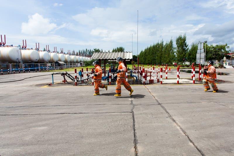 Pompiers combattant un feu faisant rage avec les flammes énormes du bois de construction brûlant photos stock
