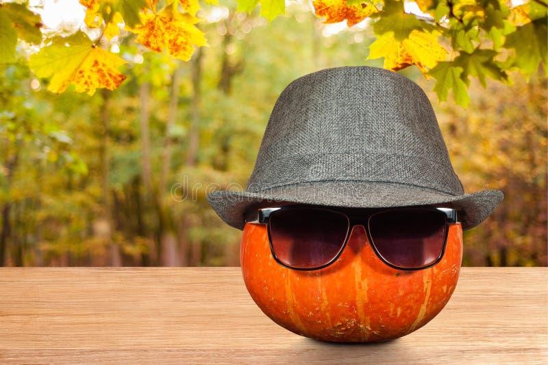 Pompoen in een hoed en zonnebril op een lijst royalty-vrije stock foto's