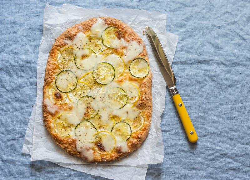Pompoen en courgettepizza op een blauwe achtergrond, hoogste mening stock afbeeldingen
