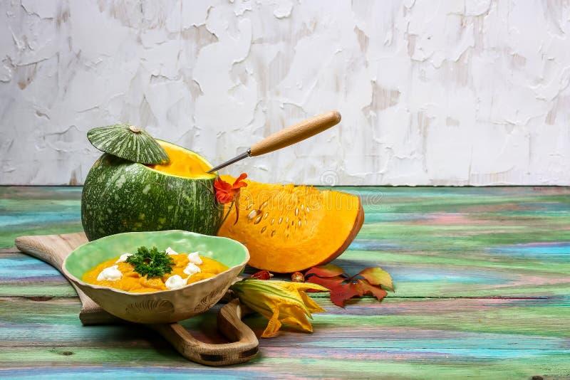 Pompoen en wortelsoep in groene pompoen, tadka met room en peterselie op houten achtergrond wordt voorgesteld die stock fotografie