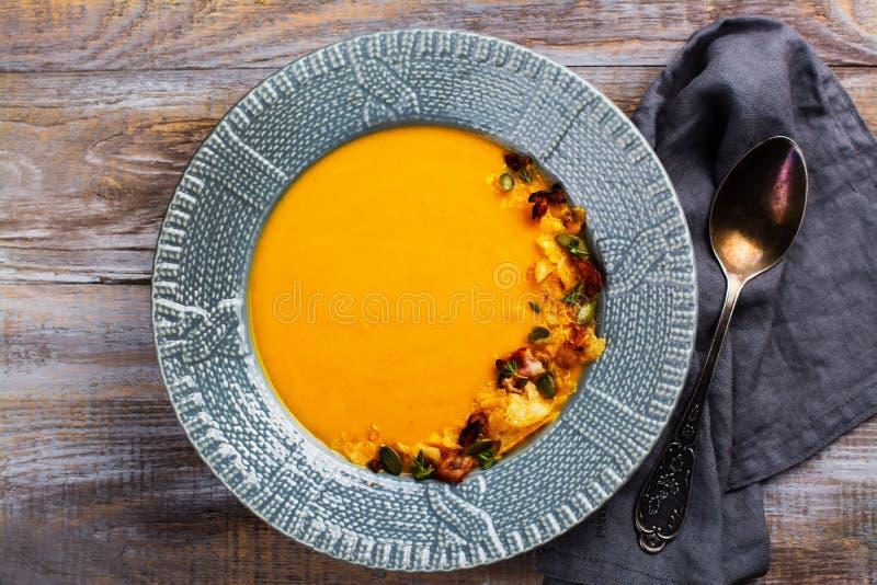 Pompoen en wortelsoep met pompoenzaden wordt gediend, chips die stock fotografie