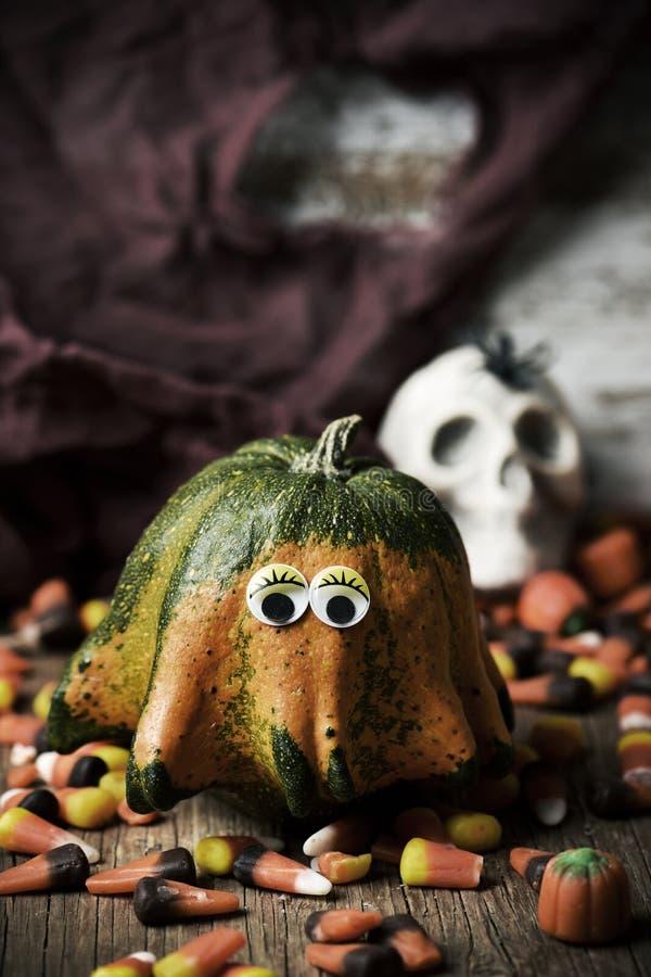 Pompoen met grappige ogen, suikergoed en schedel royalty-vrije stock afbeelding