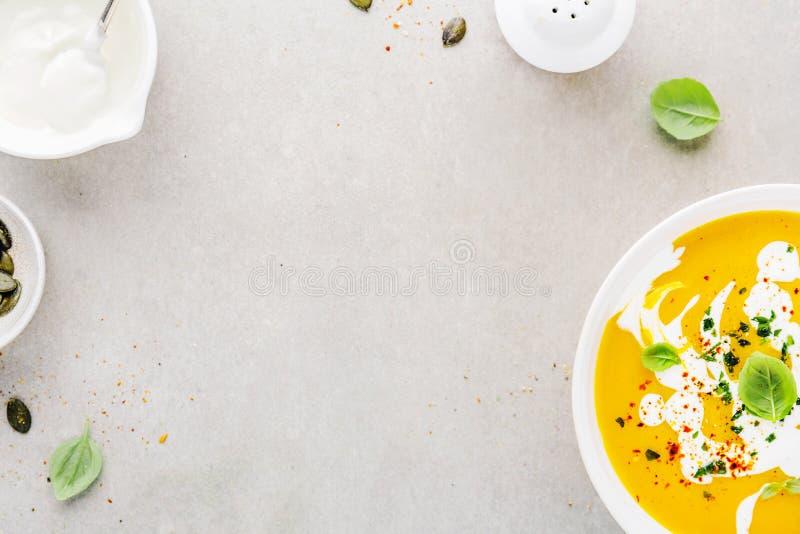 Pompoen romige die soep in kom wordt gediend stock afbeeldingen