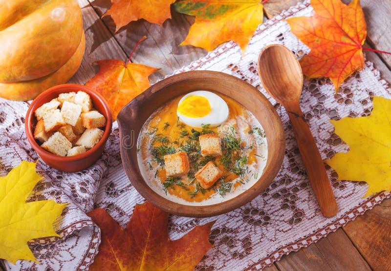Pompoen room-soep met esdoornbladeren, gekookt ei en c wordt verfraaid dat royalty-vrije stock foto