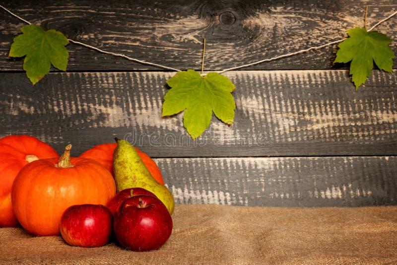 Pompoenen, appelen en peer op jutezak stock afbeelding