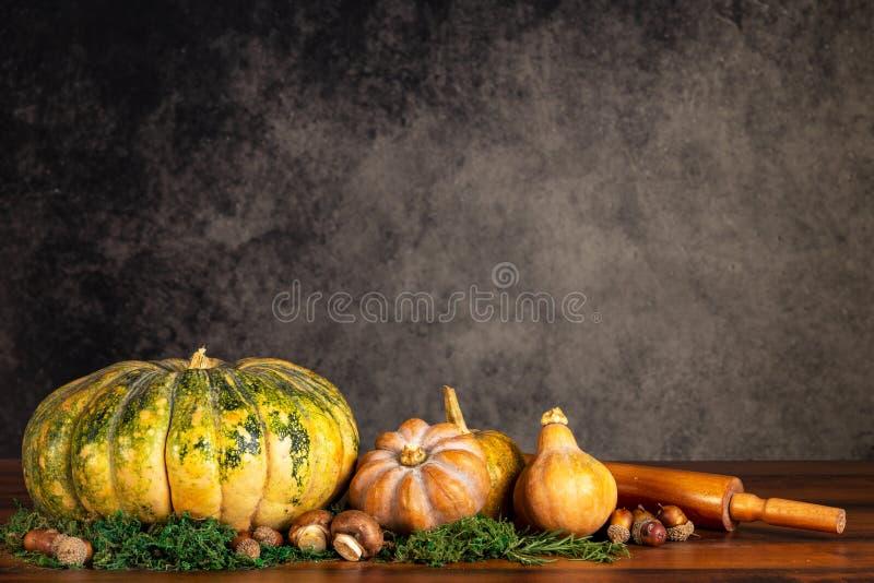 Pompoenen, butternuts en paddestoelen met deegrol op een lijst over een uitstekende achtergrond met exemplaarruimte royalty-vrije stock afbeeldingen