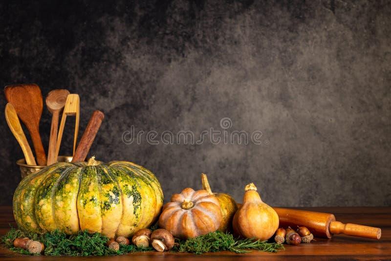 Pompoenen, butternuts en paddestoelen met het koken ustencils en deegrol op een lijst over een uitstekende achtergrond met exempl royalty-vrije stock foto's