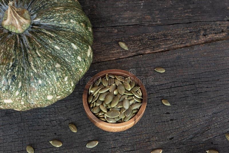 Pompoenkorrel in houten kom en vers pompoenfruit op klassieke houten lijstachtergrond, graangewas stock fotografie