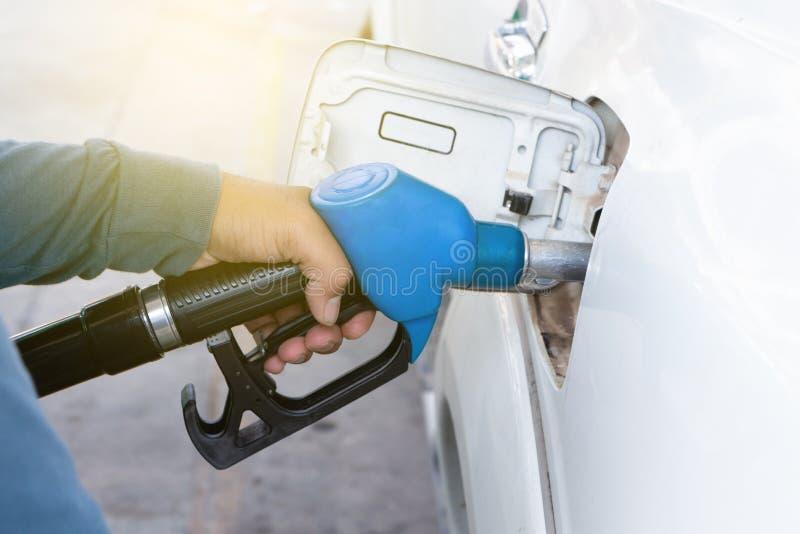 Pompować benzynę przy benzynową stacją w pojazd wręcza używać paliwowego nozzle przy benzynową stacją SKRYTKI PROWADNIKOWY poj?ci obraz stock
