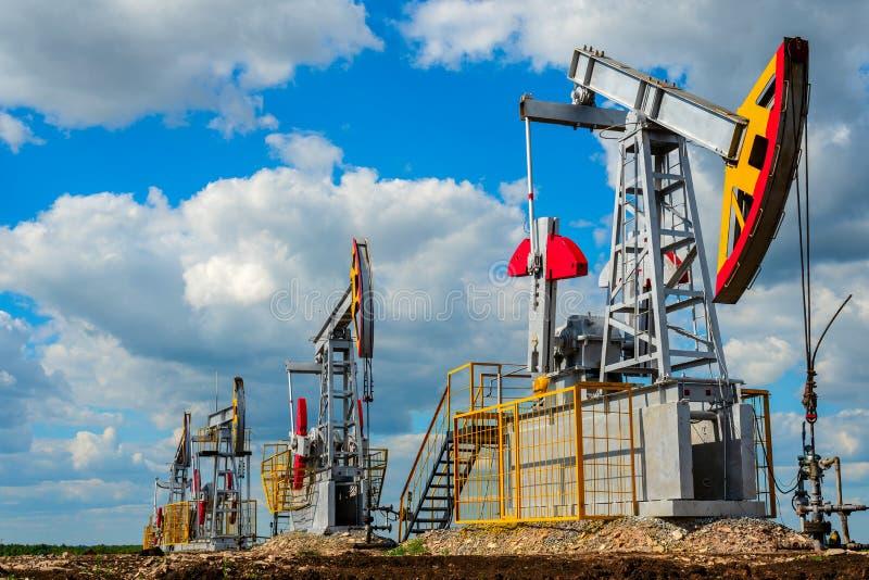 Pompstations voor olie en aardgasproductie tegen de wolkenhemel stock afbeeldingen