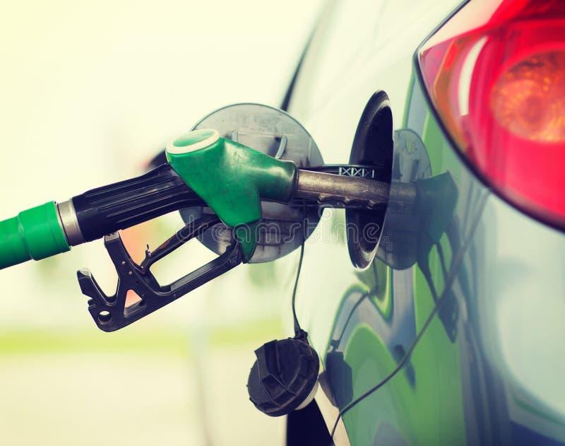 Pompujący benzynę tankuje w samochodzie przy benzynową stacją obraz royalty free