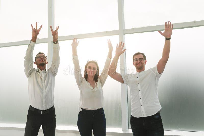 Pomyślni biznes drużyny stojaki z rękami w górę zdjęcie stock