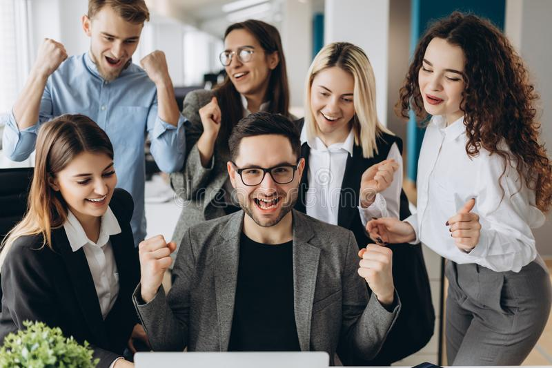 Pomyślni młodzi ludzie biznesu podnoszą ręki w pięściach i krzyczą z szczęściem podczas gdy pracujący z komputerem w biznesie obraz royalty free