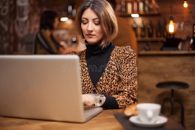 Pomyślny bizneswoman pisać na maszynie na jej laptopie obok jej kawy w rocznika pubie zdjęcie stock