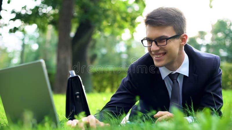 Pomyślny młody kierownika lying on the beach na zielonej trawie ono uśmiecha się i gawędzi na laptopie, zdjęcia stock