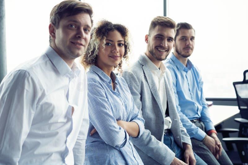 Pomyślna życzliwa drużyna z szczęśliwymi pracownikami w biurze fotografia stock