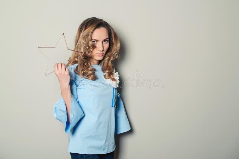 Pomyślna atrakcyjna młoda kobieta na szarości ściany tle obraz stock