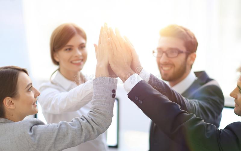 Pomyślna biznes drużyna daje each inny wysokości, stoi w biurze obraz royalty free