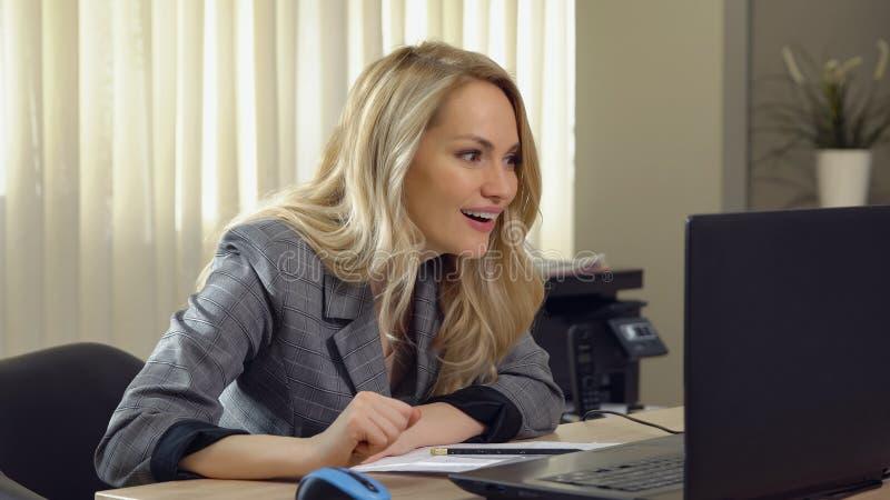 Pomyślna biznesowa kobieta w kostium dziewczyny spojrzeniach przy monitorem i radujących się obrazy royalty free