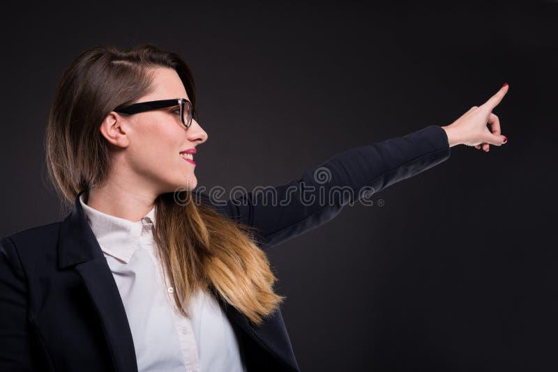 Pomyślna formalna kobieta wskazuje coś daleko od zdjęcie stock