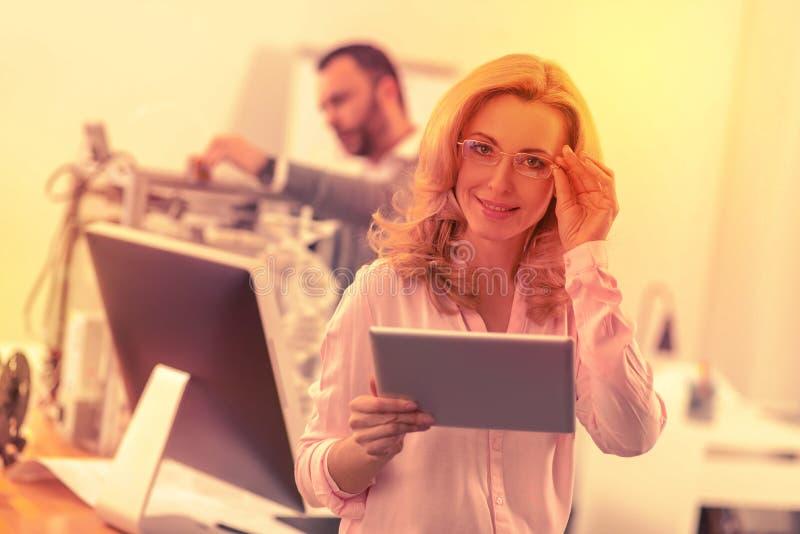 Pomyślna inteligentna dama z szkłami pozuje dla kamery fotografia royalty free