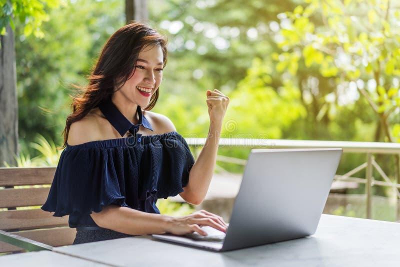 Pomyślna kobieta używa laptop z rękami podnosić zdjęcia stock