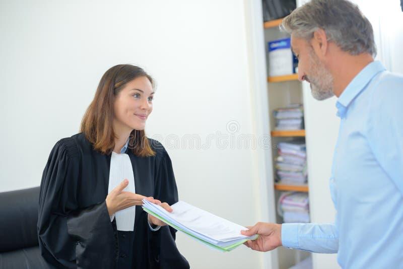 Pomyślna sędzia kobieta pokazuje dokument prawnego fotografia stock