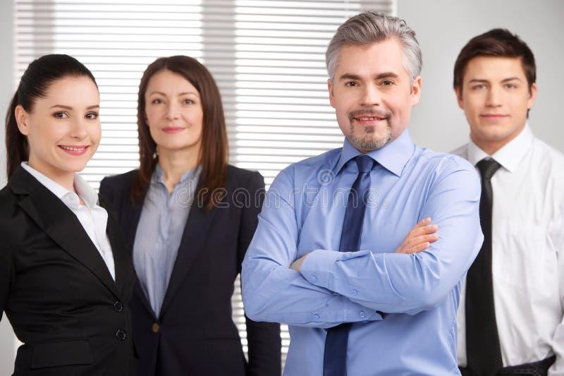 Pomyślna starsza biznesmen pozycja na pierwszoplanowym i uśmiechniętym obrazy royalty free