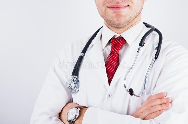 Pomyślna uśmiechnięta samiec lekarka w medycznym żakiecie z czerwonym krawatem i fonendoskopem krzyżował jego ręki nad klatką pie zdjęcia stock