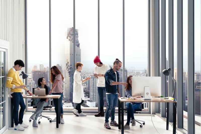 Pomyślna wieloetniczna biznes drużyna w pozyci, obsiadaniu i opowiadać wpólnie przy nowożytnymi biur wi rutynowej pracy stylu życ obrazy royalty free