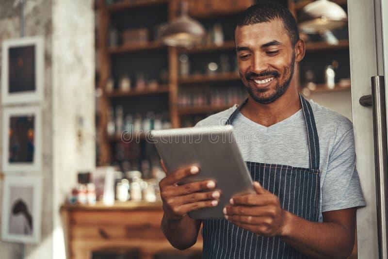 Pomyślnego barista cukierniany właściciel patrzeje cyfrową pastylkę obrazy stock