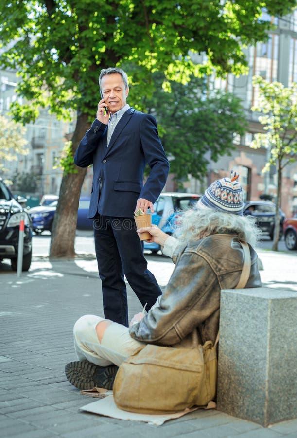 Pomyślnego biznesmena pomaga bezdomny podczas gdy mówjący telefonem zdjęcia royalty free