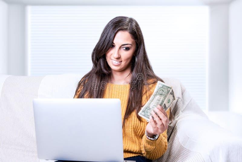 Pomyślnego młodego biznesowej kobiety mienia pieniądze dolarowi rachunki w ręce zdjęcie royalty free