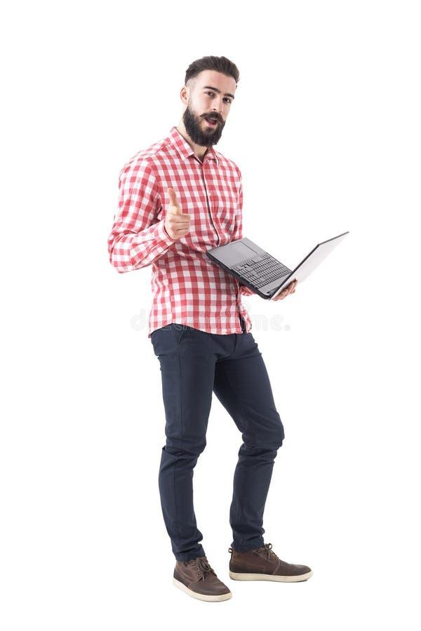 Pomyślnego młodego brodatego modnisia biznesowy mężczyzna wskazuje palec przy tobą na laptopie zdjęcia royalty free