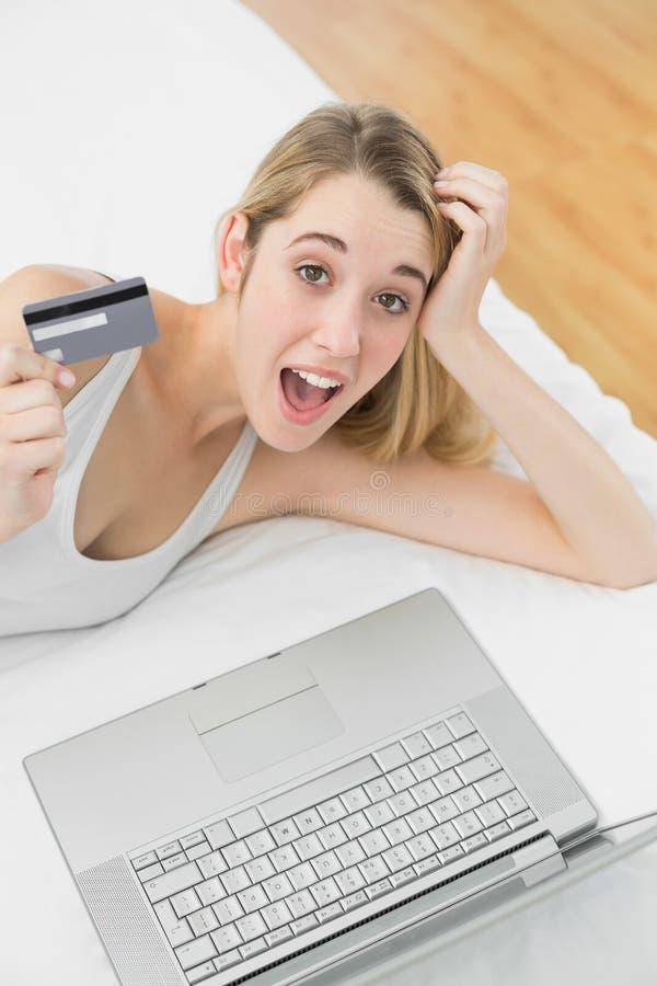Pomyślnej zdziwionej kobiety domowy zakupy z jej notatnikiem patrzeje kamerę obraz stock