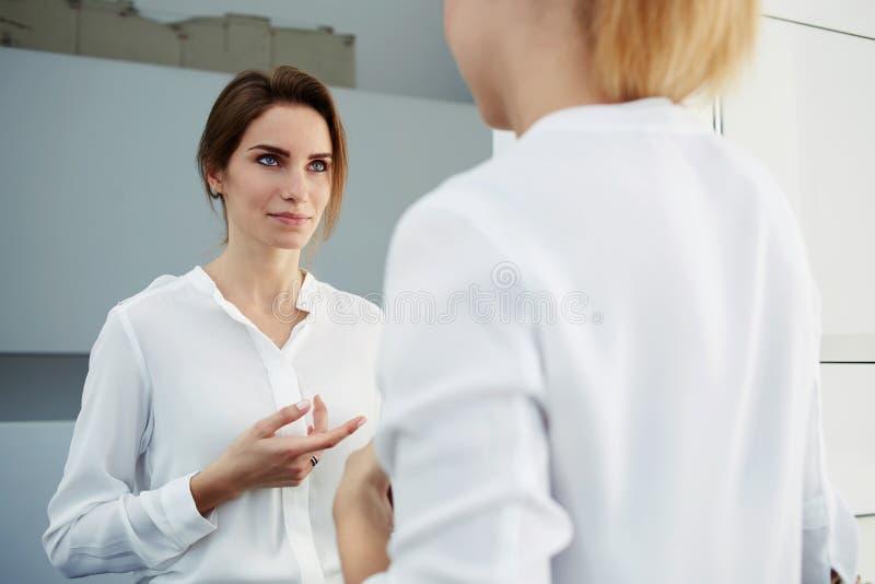 Pomyślni bizneswomany spotykający w biurowym korytarzu i zatrzymujący opowiadać o konferenci z znacząco klientami, obrazy stock