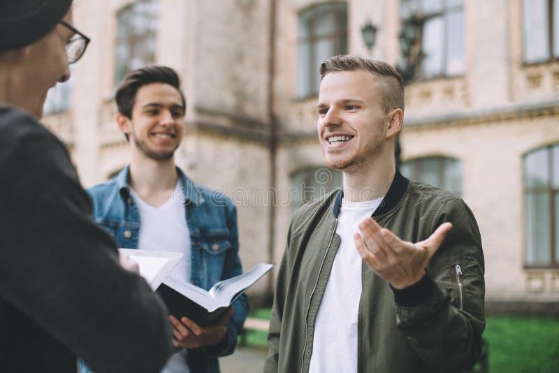 Pomyślni szczęśliwi ucznie stoi blisko kampusu lub uniwersyteta outside obrazy stock