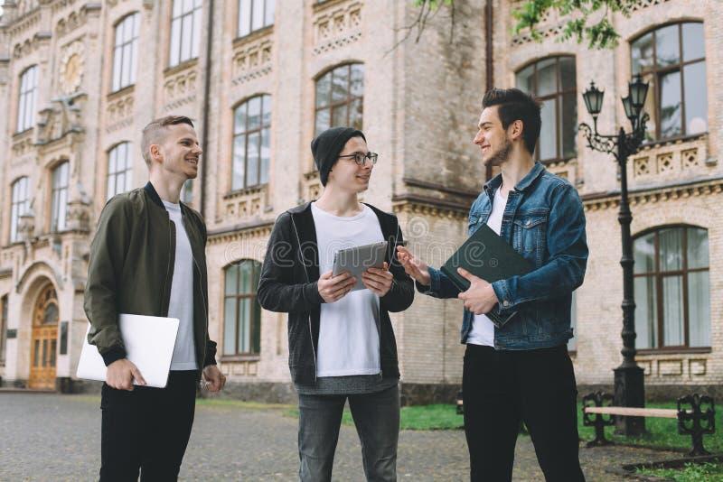 Pomyślni szczęśliwi ucznie stoi blisko kampusu lub uniwersyteta outside zdjęcia stock