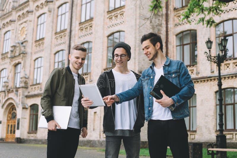 Pomyślni szczęśliwi ucznie stoi blisko kampusu lub uniwersyteta outside obraz royalty free