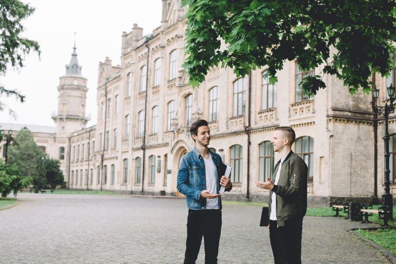 Pomyślni szczęśliwi ucznie stoi blisko kampusu lub uniwersyteta outside obraz stock
