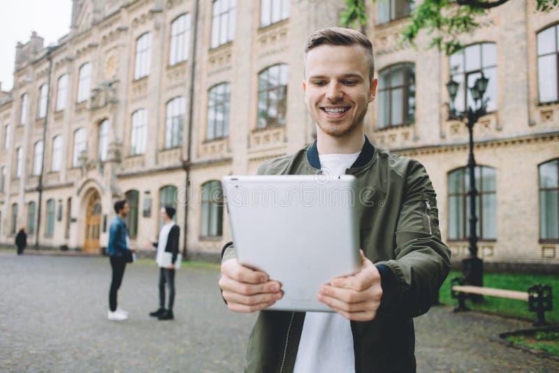 Pomyślni szczęśliwi ucznie stoi blisko kampusu lub uniwersyteta outside zdjęcie royalty free